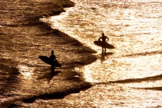 Limited Edition: Surfers return to shore at Blackhead Beach, Dunedin, New Zealand.