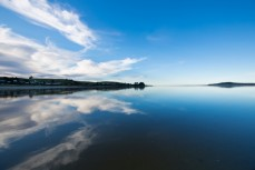 Calm water reflects the sky at Taieri Rivermouth, Dunedin, New Zealand.