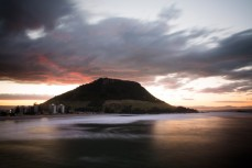 Troubled skies over Mauao (Mount Maunganui) as the sun sets, Bay of Plenty, New Zealand.