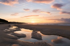 Sunrise reflected in tidal sand pools at St Clair Beach, Dunedin, New Zealand.