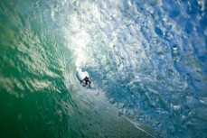 A surfer peers into a tube at Blackhead Beach, Dunedin, New Zealand.