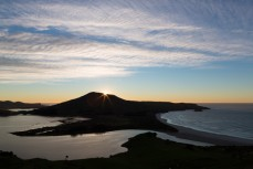 The sun peeks over the highest point (400m) on the Cape Saunders land mass on Otago Peninsula, Dunedin, New Zealand.