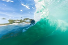 A surfer, shotfrom within the wall of the wave, rides inside the barrel at Blackhead Beach, Dunedin, New Zealand.