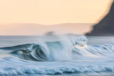 Clean hollow waves on dusk at St Kilda, Dunedin, New Zealand.